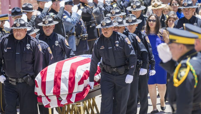 Pallbearer's brings the casket out followed by widow Alyssa R. Cordova during a funeral for Officer Jesus Cordova at Nogales High School on May 5, 2018. Cordova was gunned down by a robbery suspect last week.
