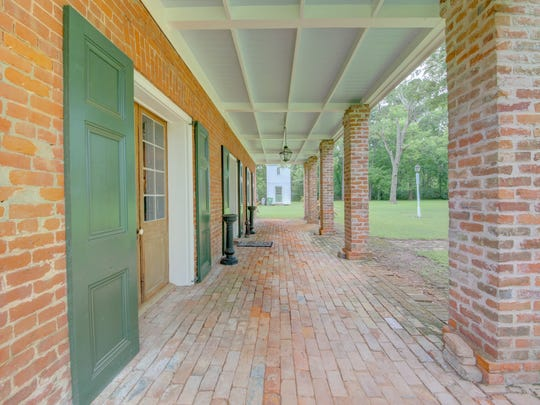 An antique brick walkway stretches across the entrance of the house.