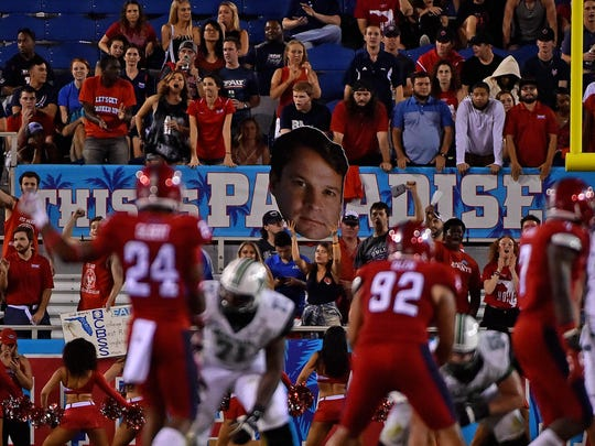 Florida Atlantic Owls fans hold up a big head likeness of head coach Lane Kiffin during the second half in the game against the Marshall Thundering Herd at FAU Football Stadium in Boca Raton, Fla., on Nov. 3.