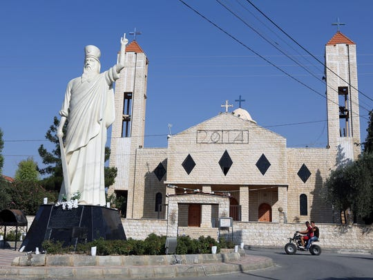 Two young men ride a motorcycle past a church in Lebanon's Christian village of Ras Baalbek in the northern Bekaa region near the border with Syria. Across the Middle East, Christian communities as old as the religion itself feel their very survival is at stake, threatened by militants of the Islamic State group rampaging across Iraq and Syria. Many Christian villagers are setting up self-defense units to protect themselves against attack. In Qaa and Ras Baalbek, two Christian northeastern villages on the border with Syria, many of the thousands of expatriates who used to spend the summer there stayed away this year.