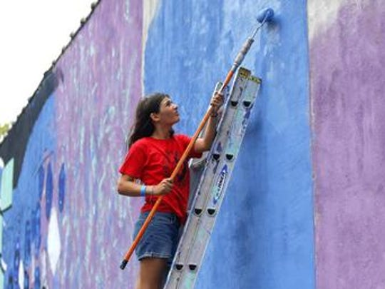 Artist work on Broad Street mural in Red Bank,NJ. Sunday,