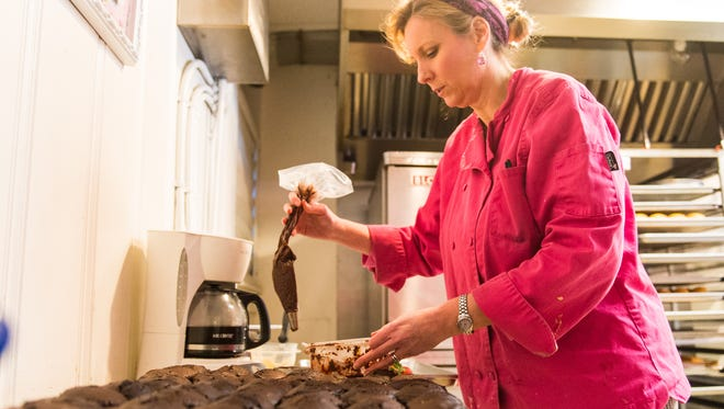 Susan Patt, owner of Cake Art, puts finishing touches on an assortment of chocolate cupcakes on Tuesday, Jan 26 at her bakery in Salisbury.
