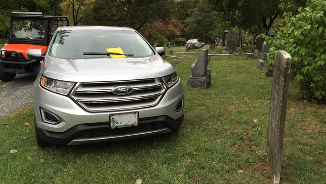 This car with Maine license plates was parked on the cemetery's burial grounds.