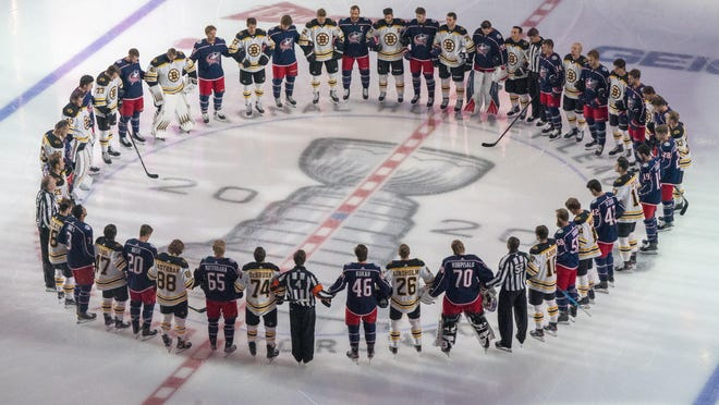 The Boston Bruins and the Columbus Blue Jackets stand together for the national anthems prior to NHL hockey exhibition game action in Toronto, Thursday, July 30, 2020.