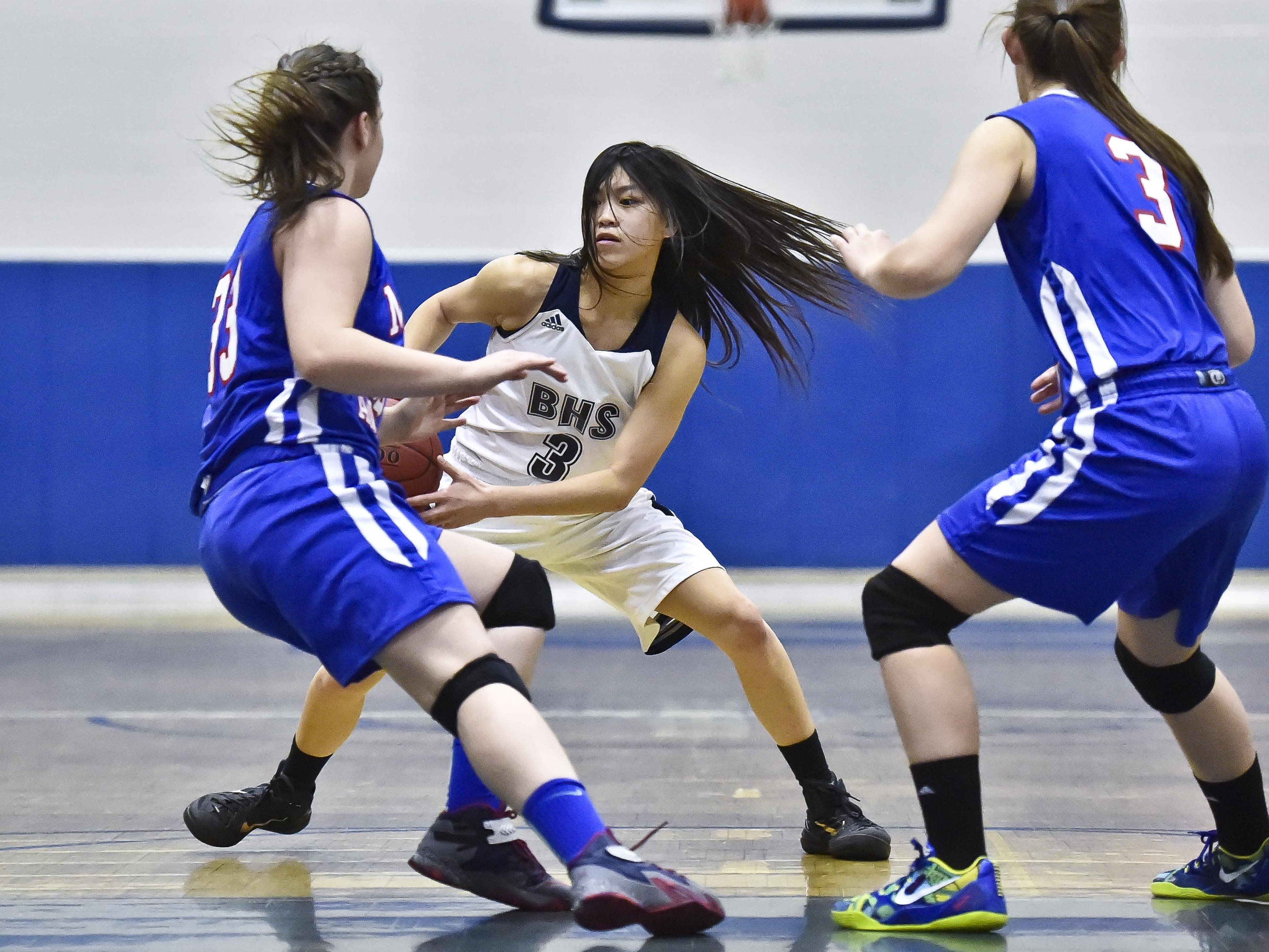 Burlington's Hien Thach (center) tries to get past Mt. Anthony's Emily Hutton (left) and Madison Little in Burlington on Tuesday, December 23, 2014.