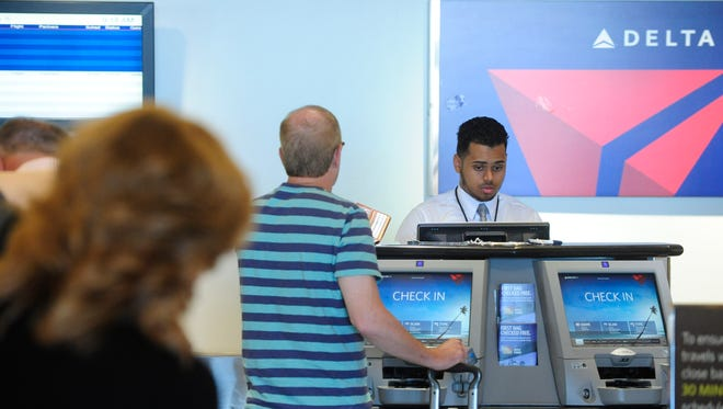 Delta Airline passengers at Louisville International Airport reschedule their flights after the airline's nationwide servers crashed, stranding passengers and delaying flights.08 August 2016