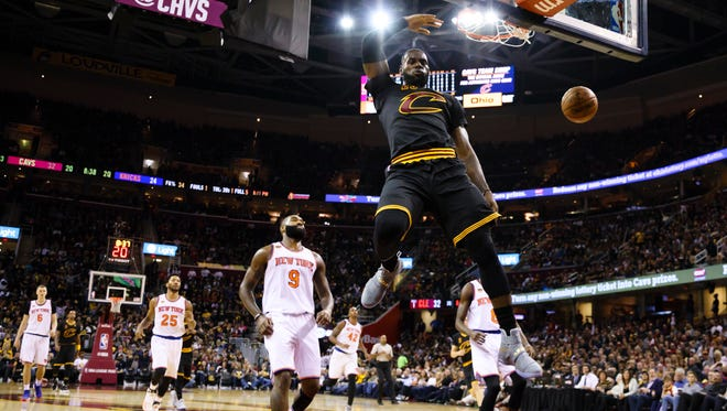 LeBron James throws down a fastbreak dunk in the Cavs' home opener.