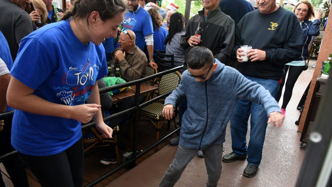 Guest of honor Anthony Nieto, 12, dances with an admirer. Over 250 cyclists participated in the Tour de Taverns on a rainy Saturday, raising funds to help a family in need.