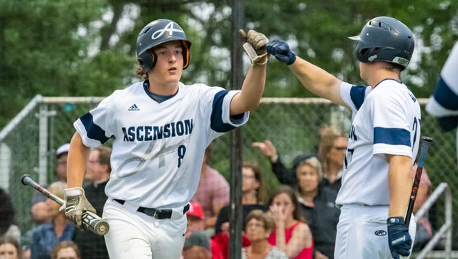 Cole Simon gets a high five after scoring a run as the Ascension Blue Gators take on Catholic High New Iberia. Friday, April 13, 2018.