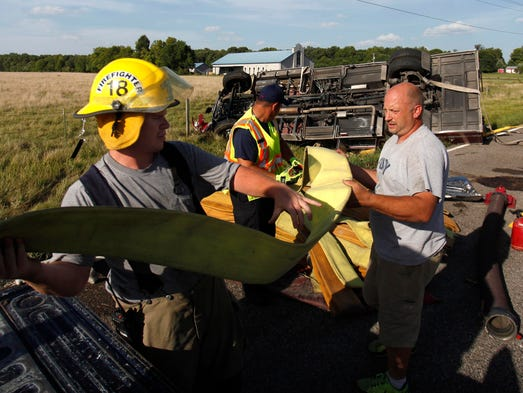 Firefighters from Ebenezer load fire hose into a truck after a fire truck overturned on Greene County WW east of Missouri 13 on Thursday, August 21, 2014.