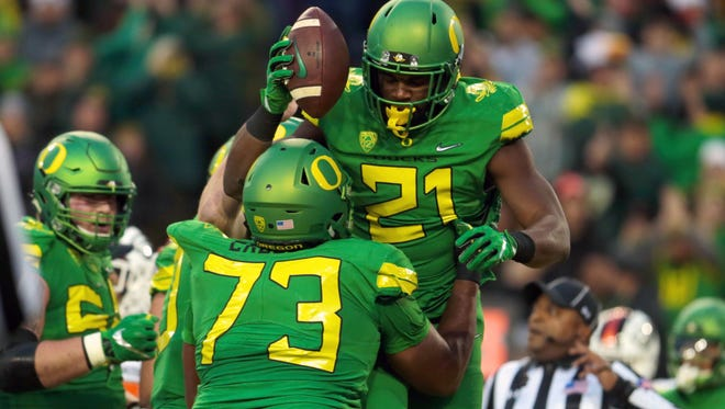 Oregon Ducks running back Royce Freeman (21) celebrates a touchdown with quarterback Justin Herbert (10) and offensive lineman Tyrell Crosby (73) against the Oregon State Beavers in the first quarter at Autzen Stadium.