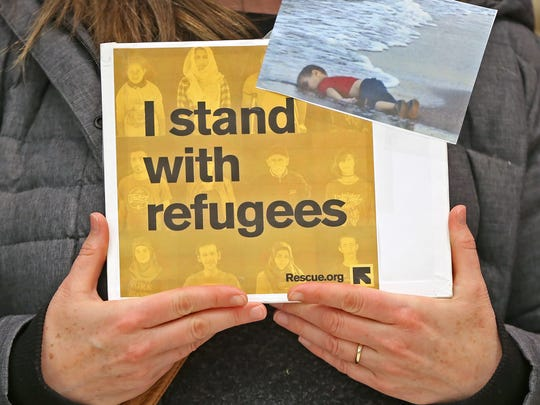 A woman holds a sign showing support of refugees and