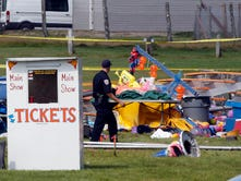 Investigators inspect the site of a circus tent that collapsed Monday during a show by the Walker Brothers International Circus at the Lancaster Fair grounds in Lancaster, N.H. Tuesday Aug. 4, 2015. A quick moving storm with 60 mph winds hit the tent shortly after the show started killing a father and daughter. (AP Photo/Jim Cole)