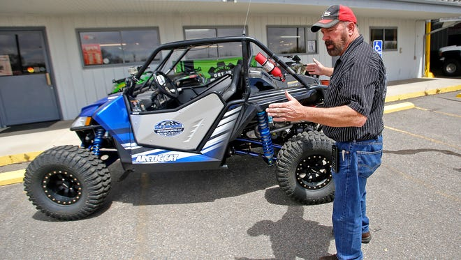 Dunlap Performance And Motorsports LLC owner and operator Darryl Dunlap talks about how to make an off-road vehicle street legal Thursday at his shop in Farmington.