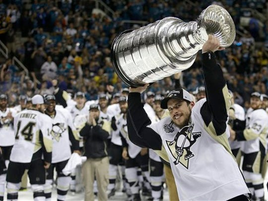 Pittsburgh Penguins center Sidney Crosby raises the