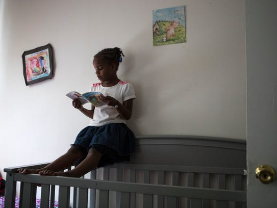 Taralyn Drew, 6, reads while propped over her sister's