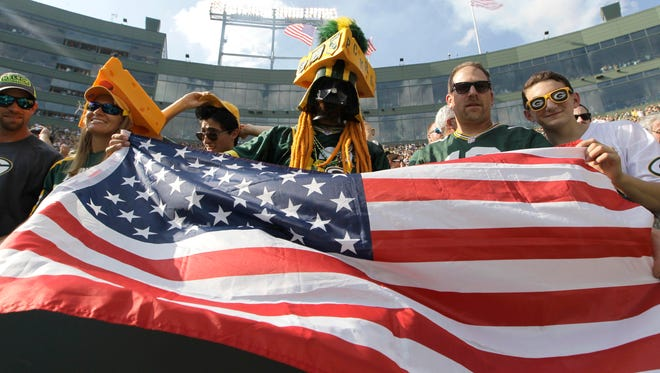 Green Bay Packers fans wave the American flag following the national anthem on Sunday.