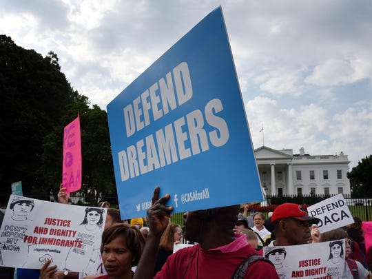 Protesters hold up signs during a rally supporting Deferred Action for Childhood Arrivals, or DACA, outside the White House on Tuesday, Sept. 5, 2017. Thousands are expected to gather for rallies on Tuesday, when President Donald Trump is slated to announce the program's future. (Olivier Douliery/Abaca Press/TNS)