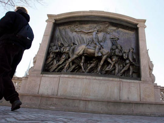 People walk past the memorial to Union Col. Robert Gould Shaw and the 54th Massachusetts Volunteer Infantry Regiment, near the State House in Boston.