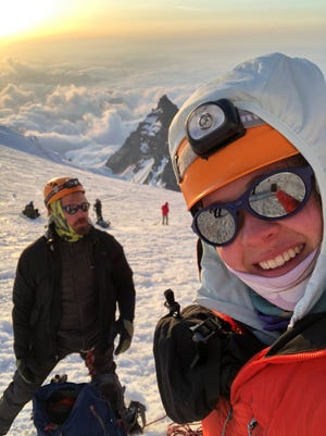 Lauren Richards grabs a selfie with her brother Jordan Childs in the background on the slopes of Mount Rainier.