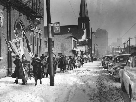 """Detroit's Mexican colony prayed and paraded in December 1951 in homage to """"Our Lady of Guadalupe"""". The celebration marked the appearance 420 years ago of the Virgin Mary before Juan Diego, a Mexican Indian. The group marched down Bagley in the bitter cold from Holy Trinity Church to St. Vincent De Paul where they attended high mass."""