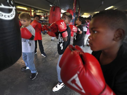 Three young boxing students work the same bag at SIMS