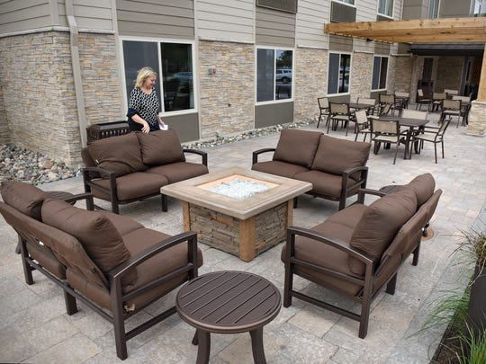 Country Inn & Suites St. Cloud-West General Manager Jackie Klehr adjusts the cushions on some outdoor furniture Tuesday, Sept. 13, in the hotel's new outdoor seating area. The hotel recently finished a renovation and 30-room expansion.