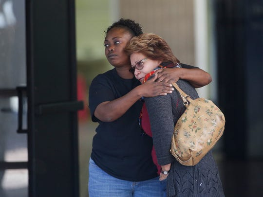Two women embrace at a community center where family