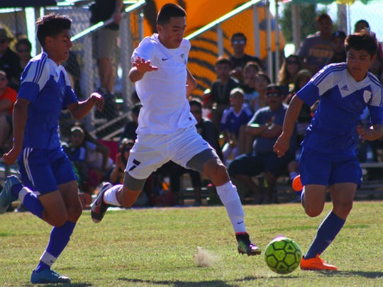 Alamogordo's Julian Torres, center, dribbles the ball up field while being pursued by two Los Lunas defenders Saturday afternoon.