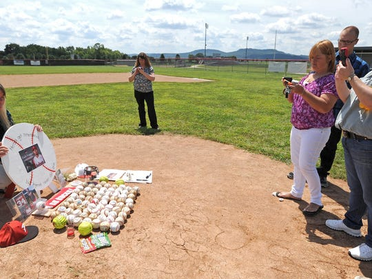 Zach Farmer's mother, Tammy Farmer, left, views a memorial set up in his honor on the pitching mound of the Piketon High School baseball field Saturday during the viewing held for him at the high school.