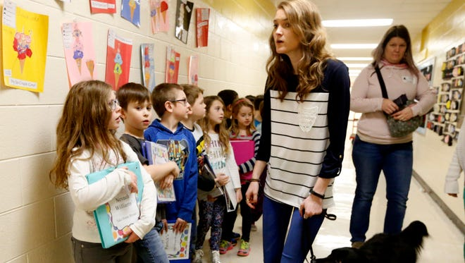 Paige Saylors, a second grade Christiana Elementary school teacher, who is legally blind, walks the hallway with her class and her service dog Inca, on Wednesday, Jan. 24, 2018.
