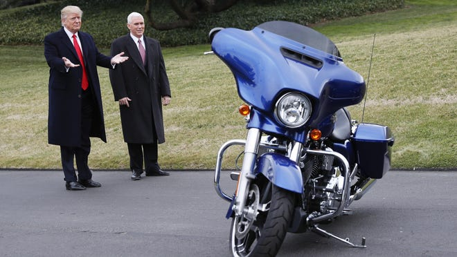 President Donald Trump and Vice President Mike Pence stop to admire a Harley-Davidson motorcycle parked on the South Lawn of the White House in February 2017 as he welcomed Harley-Davidson executives and union representatives.