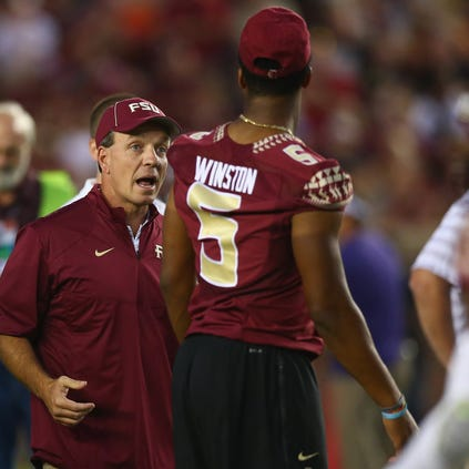 FSU coach Jimbo Fisher talks with Jameis Winston before the game against the Clemson Tigers at Doak Campbell Stadium.