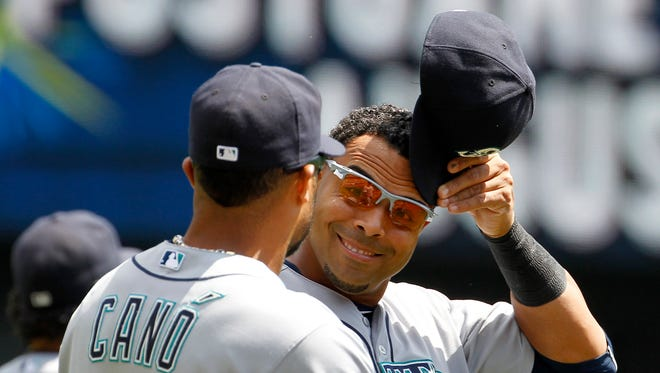 Seattle Mariners right fielder Nelson Cruz, right, talks with designated hitter Robinson Cano (22) before a baseball game against the Minnesota Twins in Minneapolis, Sunday, Aug. 2, 2015.