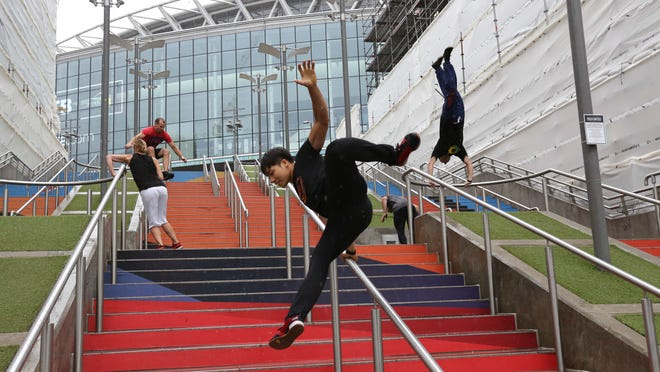 In this Aug. 16, 2018 file photo, participants of the Parkour Generations work on their practice runs outside of Wembley Stadium ahead of the 13th Rendezvous International Parkour Gathering in London. Global organizers of parkour are urging the IOC not to add the street-running sport to the 2024 Paris Olympics at a meeting next week.