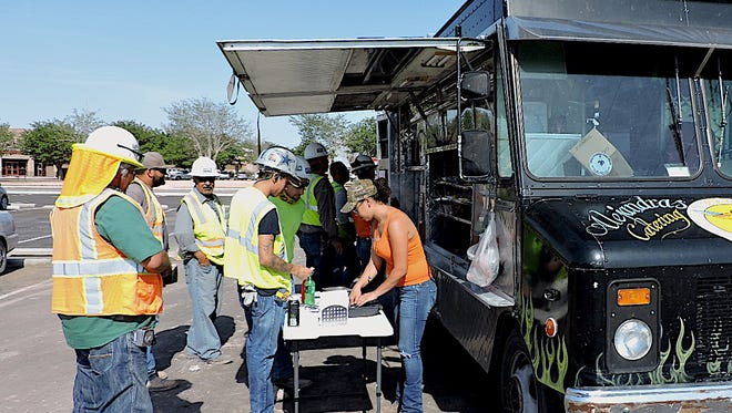 Workers at the new Deming High School construction site line up during their lunch break for authentic Chihuahua-style food and cold drinks at Alejandra's Catering truck.