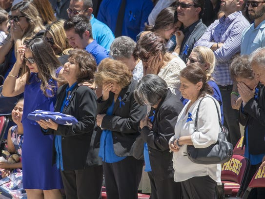 Widow Alyssa R. Cordova, second to the left, cries