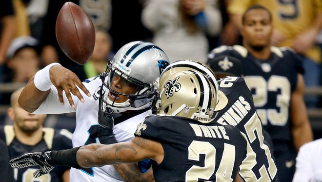 Carolina Panthers quarterback Cam Newton (1) fumbles out of bounds as he is hit by New Orleans Saints cornerback Corey White (24) and free safety Malcolm Jenkins (27) during the first quarter of a game at Mercedes-Benz Superdome.