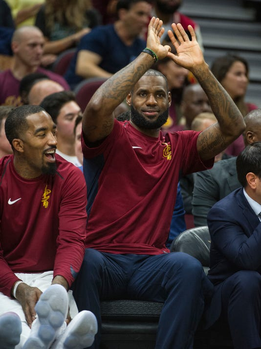 Cleveland Cavaliers' LeBron James, right gets a laugh out of JR Smith during the second half of an NBA preseason basketball game against the Atlanta Hawks in Cleveland, Wednesday, Oct. 4, 2017. James did not play in the Cavaliers 109-93 loss to the Hawks. (AP Photo/Phil Long)