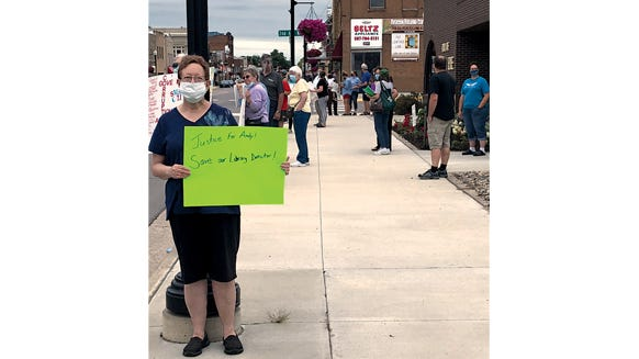 Supporters of Library Director Andrew Kelton gathered outside City Hall during the City Council meeting Wednesday evening, Aug. 5.