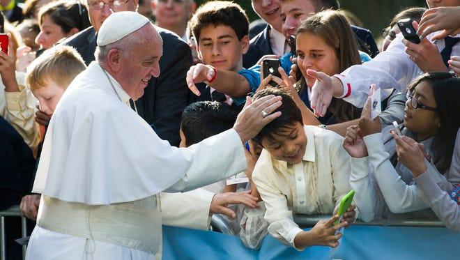 Pope Francis places his hand on a young boys head while the boy takes a selfie before the Pope departs the Apostolic Nunciature, the Vatican's diplomatic mission in the heart of Washington, en route to the Capitol to address a joint meeting of Congress Thursday.