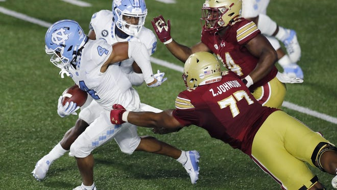 North Carolina defensive back Trey Morrison, left, evades Boston College offensive lineman Zion Johnson after intercepting a two-point conversion attempt in the final minute of Saturday's game at Alumni Stadium.