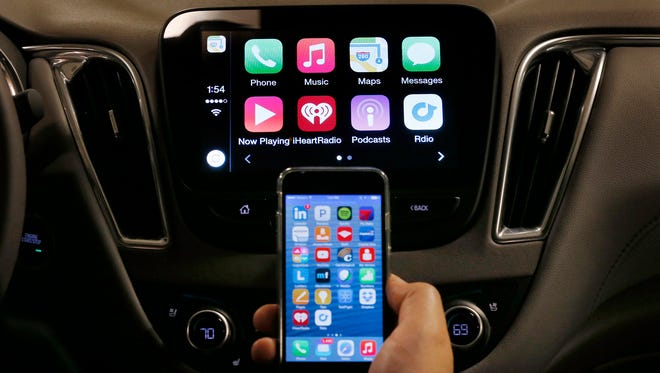 An iPhone is connected to a 2016 Chevrolet Malibu equipped with Apple CarPlay apps, displayed on the car's MyLink screen. With 220 million Internet connected cars expected to be on the roads within five years, a national security expert on Tuesday, April 12, 2016, urged automakers to be mindful of the growing cyber-security threats posed by terrorists, information crooks and spies who could potentially try to hack into wired vehicles.