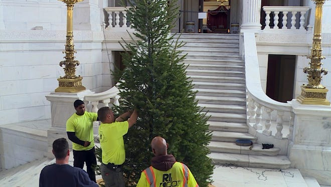 In this still image from video provided by WPRI 12, workers surround a Christmas tree in the Statehouse rotunda Nov. 22 in Providence, R.I. The 14-foot tree was removed after staff decided it was too small in the rotunda. A 20-foot tree was obtained to replace it.