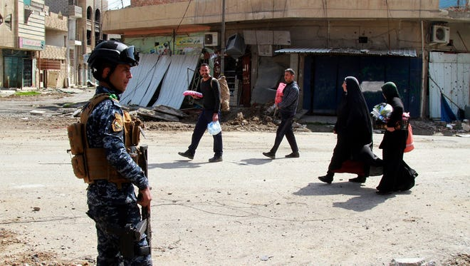 Iraqi displaced people walk next to an Iraqi policeman during a military operation against the Islamic state group at old city district in central Mosul, Iraq, on March 29, 2017.