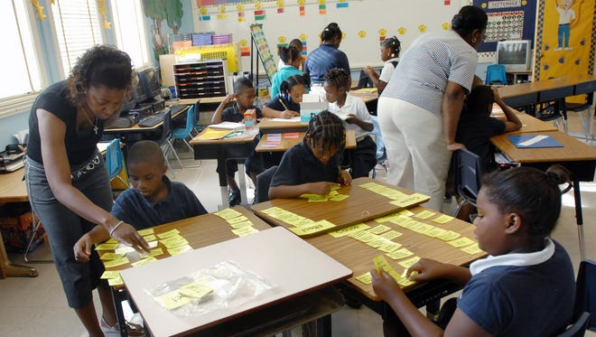 In this 2010 photo, teachers work with third-grade students at George Elementary School in Jackson.