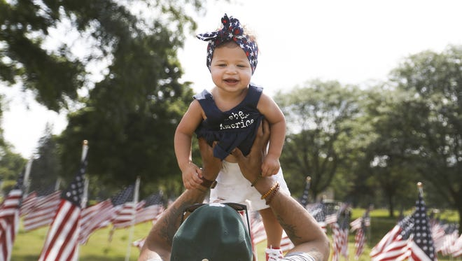 Jimmy Hurt throws his 15-month-old daughter, Nora, in the air to get her to smile at the Field of Flags at Oaklawn Memorial Gardens on Monday, July 2, 2018.