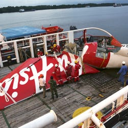 Workers prepare to unload the newly-recovered tail section of crashed AirAsia Flight 8501 at Kumai port in Pangkalan Bun,  Indonesia, on Jan. 11, 2015.