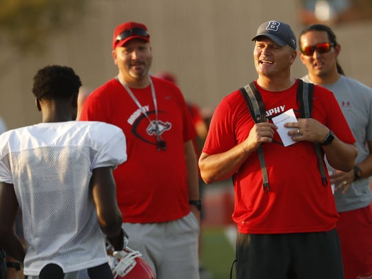 Brophy Prep head coach Jon Kitna talks with his team during an exhibition on Aug. 9.