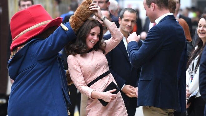 Duchess Kate dances with Paddington Bear as Prince William watches during a charities event at Paddington train station in London on Oct. 16, 2017.